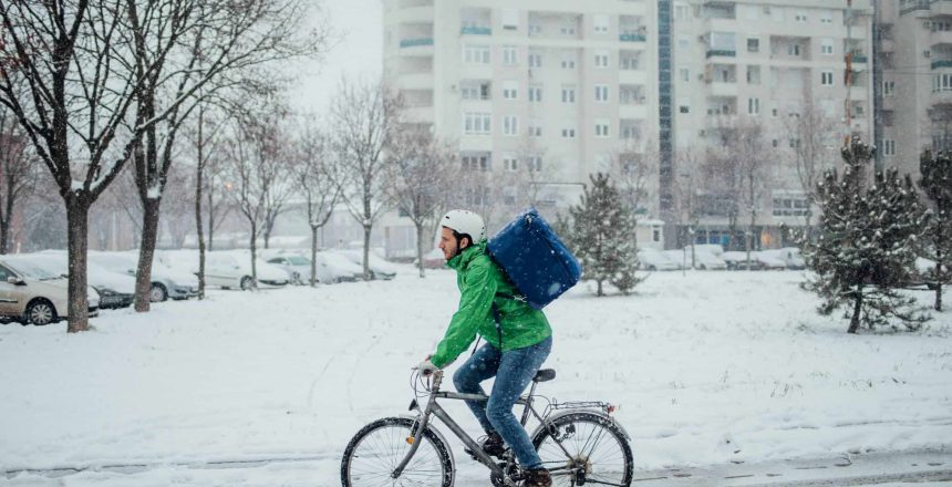 Delivery boy on a bike in a snowy day